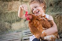 A young girl holding a chicken in a henhouse. Stock Photo - Premium Royalty-Freenull, Code: 6118-07203310