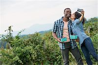 Picking blackberry fruits on an organic farm. A couple taking a selfy with a smart phone, and fruit picking. Stock Photo - Premium Royalty-Freenull, Code: 6118-07203678