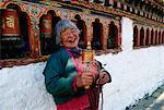 An old woman with prayer wheels laughing at the Kyichu Buddhist Temple in Paro, Bhutan Stock Photo - Premium Rights-Managed, Artist: Robert Harding Images, Code: 841-07204833
