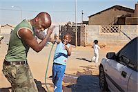 Boy spraying water on father by car Stock Photo - Premium Royalty-Freenull, Code: 6110-07233633