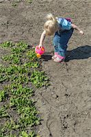 Girl watering plants with her watering can Stock Photo - Premium Royalty-Free, Artist: Blend Images, Code: 653-07233762