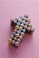 represented - A large group of batteries arranged into the shape of an arrow, pointing up Stock Photo - Premium Royalty-Free, Artist: Rob