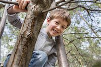 A young cheerful boy climbing a tree Stock Photo - Premium Royalty-Freenull, Code: 653-07233991