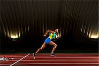 sprint - Young woman sprinting in stadium Stock Photo - Premium Royalty-Freenull, Code: 614-07234798