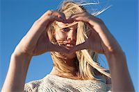 Portrait of young woman making heart sign, Breezy Point, Queens, New York, USA Stock Photo - Premium Royalty-Freenull, Code: 614-07234841