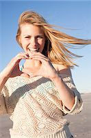 Smiling woman making heart sign with hands, Breezy Point, Queens, New York, USA Stock Photo - Premium Royalty-Freenull, Code: 614-07234843