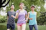 Three young people jogging in park