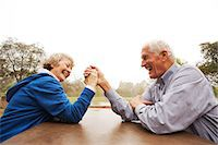 Husband and wife arm wrestling in the park Stock Photo - Premium Royalty-Freenull, Code: 614-07234949