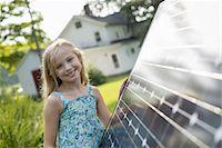 solar panel usa - A young girl beside a large solar panel in a farmhouse garden. Stock Photo - Premium Royalty-Freenull, Code: 6118-07235257