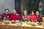 Portrait of family enjoying Chinese meal in traditional Chinese clothing