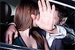 Young couple kissing in car at a red carpet event, man is shielding with his arm outstretched blocking paparazzi photographers