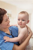 Smiling doctor holding baby in her arms in the doctors office Stock Photo - Premium Royalty-Freenull, Code: 6116-07236024