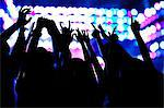Audience watching a rock show, hands in the air, rear view, stage lights