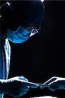 Two surgeons working and passing surgical equipment in the operating room, dark, close-up Stock Photo - Premium Royalty-Freenull, Code: 6116-07236160