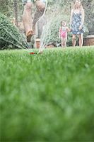 Surface level shot of father jumping through a sprinkler in the grass, mother and daughter watch in the background Stock Photo - Premium Royalty-Freenull, Code: 6116-07236227