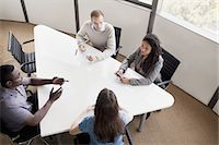Four business people sitting at a conference table and discussing during a business meeting Stock Photo - Premium Royalty-Freenull, Code: 6116-07236444