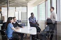 Five business people sitting at a conference table and discussing during a business meeting Stock Photo - Premium Royalty-Freenull, Code: 6116-07236446
