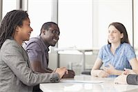 Three business people sitting at a conference table and discussing during a business meeting Stock Photo - Premium Royalty-Freenull, Code: 6116-07236452