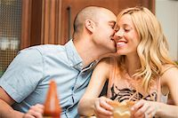Young man kissing young woman on cheek, sitting and eating in home, Canada Stock Photo - Premium Rights-Managednull, Code: 700-07237598