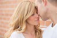 Close-up portrait of young couple standing in front of brick wall outdoors, nose to nose and