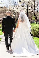 Backview of bride in wedding gown with bridegroom, holding hands and walking down pathway in park in Spring on Wedding Day, Canada Stock Photo - Premium Rights-Managednull, Code: 700-07237612