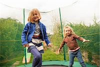 Girls playing on trampoline Stock Photo - Premium Royalty-Freenull, Code: 649-07238335