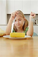 sad child sitting - Girl poking at corn cob on plate Stock Photo - Premium Royalty-Freenull, Code: 649-07238339