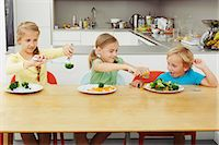 Girls scooping vegetables onto boy's plate Stock Photo - Premium Royalty-Freenull, Code: 649-07238341