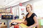 Woman working in organic food market, serving at cash register Stock Photo - Premium Royalty-Freenull, Code: 649-07238423