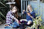 Two girls in garden planting seeds into pots Stock Photo - Premium Royalty-Freenull, Code: 649-07239021