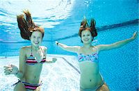 Two teenage girls swimming underwater in swimming pool Stock Photo - Premium Royalty-Freenull, Code: 649-07239174