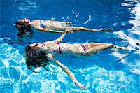 Two teenage girls floating in swimming pool Stock Photo - Premium Royalty-Freenull, Code: 649-07239175