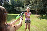 Two teenage girls firing water guns in garden Stock Photo - Premium Royalty-Freenull, Code: 649-07239177