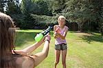 Two teenage girls firing water guns in garden Stock Photo - Premium Royalty-Freenull, Code: 649-07239177