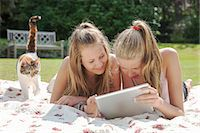 Two teenage girls on picnic blanket looking at digital tablet Stock Photo - Premium Royalty-Freenull, Code: 649-07239181