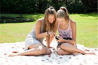 Two teenage girls on picnic blanket looking at mobile phone Stock Photo - Premium Royalty-Freenull, Code: 649-07239182