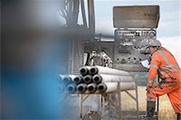 Drilling rig worker inspecting machinery Stock Photo - Premium Royalty-Freenull, Code: 649-07239194