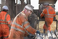 Workers in hard hats operating drilling rig Stock Photo - Premium Royalty-Freenull, Code: 649-07239200
