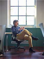 Mature businessman sitting on office chair wit cell phone Stock Photo - Premium Royalty-Freenull, Code: 649-07239298