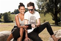 Young couple using digital tablet in park Stock Photo - Premium Royalty-Freenull, Code: 649-07239425