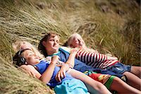 Four friends relaxing in dunes, Wales, UK Stock Photo - Premium Royalty-Freenull, Code: 649-07239478