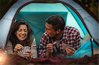 Mature couple lying together in tent, playing card game Stock Photo - Premium Royalty-Freenull, Code: 614-07239971
