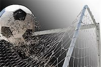 Studio shot of football powering through goal netting Stock Photo - Premium Royalty-Freenull, Code: 614-07239995