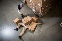 funny looking people - Woman looking at man lying on floor covered by cardboard boxes in warehouse Stock Photo - Premium Royalty-Freenull, Code: 614-07240171