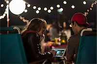 Young couple looking at digital tablet at rooftop barbecue Stock Photo - Premium Royalty-Freenull, Code: 614-07240205