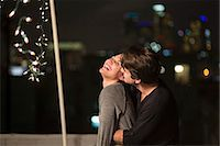 Young couple embracing at rooftop party Stock Photo - Premium Royalty-Freenull, Code: 614-07240206