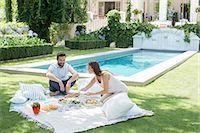 Couple enjoying picnic by pool Stock Photo - Premium Royalty-Freenull, Code: 6113-07241959