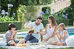 Family enjoying picnic at poolside