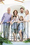 Multi-generation family smiling at balcony railing