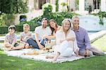Multi-generation family enjoying picnic in backyard